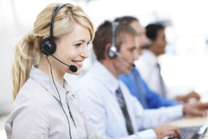 Beautiful customer services operator smiling while assisting someone, with colleagues in background - copyspace
